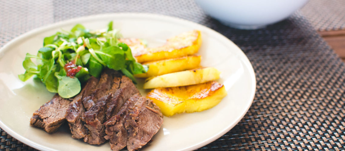 Beef steak with grilled pineapple and salad